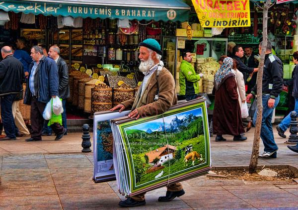 Old man slelling posters outside the Spice Bazaar in Instanbul, Turkey